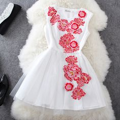 another gorgeous white mini-dress, the bright embroidered flowers make this amazing
