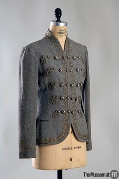 """Day Jacket, Muriel King (1900-1977) for Rodier (founded 1852): 1935, American, wool flannel with passementerie trim and metal buttons. """"The detailed tailoring and military styling of this day jacket are hallmarks of King's designs. Throughout her career, King drew from a wide range of military sources, from fifteenth-century armor to the twentieth-century sailor's collar—a version of which appears on the grey wool day dress to the left."""""""