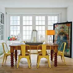 Dining Room: An ancestor portrait leaning against the wall sets the eclectic, rustic-meets-industrial tone. Formerly floorboards dining table: This one of- a-kind find is made of vintage flooring from a Romanian farmhouse atop barley twist legs. Lemon yellow chairs: The painted metal finish adds a pop of sunny color and is super easy to clean—a plus in a house with young children.