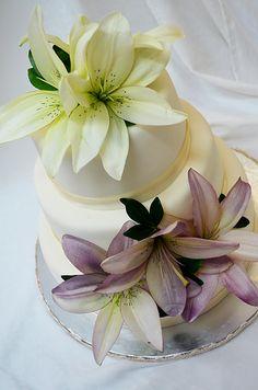 Pastel de fondant con flores lilis naturales.