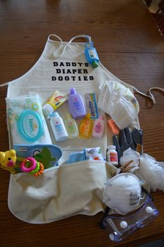 This would so fun for a co-ed baby shower - Daddy's Diaper Dooties Apron - Includes diapers, wipes, powder, 3 different baby soaps, lotion, burp cloths, bibs, baby toy, face mask, goggles, disposable gloves, reusable gloves, hand sanitizer, Tylenol, cloths pins, butt paste, destine, and ear plugs.