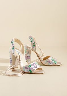 champagne heels from Betsey Johnson! Elevating the traditional pump silhouette with luxe satin fabric punctuated by purple, green, pink, and blue embroidery - along with chic ankle ties - this floral pair promises boundless delight. By the way, this lovely item will be available for purchase in February!