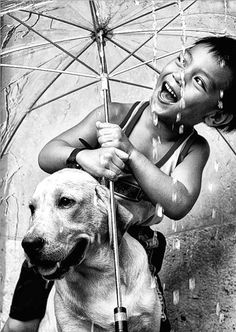 Little boy laughing and holding an umbrella of himself and a dog.  Happy child! black & white photo