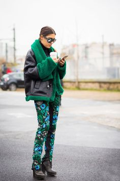 Leather and shearling jacket worn with green and blue floral pants and black leather ankle boots.