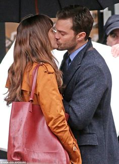 Steamy smooch: Dakota Johnson and her hunky Fifty Shades Darker costar Jamie Dornan were spotted passionately kissing as they filmed in Vancouver on Tuesday