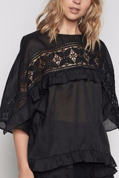 This beautiful black top has a low-key bohemian aesthetic. Wonderfully light and slightly sheer this effortless blouse has been designed with an intricate crochet lace panel that arcs through the sleeve and chest underlined by a ruffled layer that highlights the draping wide sleeve. Designed for a loose fit the top is finished at the hip with a softly ruffled hem.   Keyhole back button and loop neck closure.   Made from 65% polyester and 35% cotton cold delicate machine wash.  Trinity Top by…