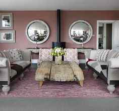 Matching Mirrors: With two matching tables, twin couches, and a convex mirror on either side of the piping, this room has a distinctly symmetrical feel — which makes the imperfect, natural edges of the rustic wooden coffee table stand out even more.  Source: The Soho Hotel
