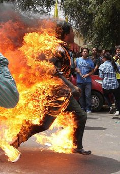 Tibetan man screams as he runs engulfed in flames after self-immolating at a protest in New Delhi, India, ahead of Chinese President Hu Jintao's visit to the country, on March 26, 2012. The man was rushed to hospital with and later died of his injuries.