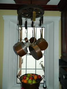 Pot Rack made from a wagon wheel and antique hanging fish scales. So cool! This hangs in a beautiful home for sale on 23+ acres on Lake Arrowhead in Georgia, VT. (Keller Williams Realty listing)
