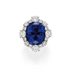 AN ATTRACTIVE SAPPHIRE AND DIAMOND RING   The oval-shaped sapphire weighing 26.26 carats to the brilliant-cut diamond cluster surround and plain hoop
