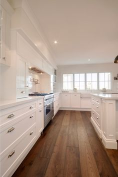 Clea white kitchen with wide hardwood plank flooring. #Kitchen #WhiteKitchen #WidehardwoodplankFlooring