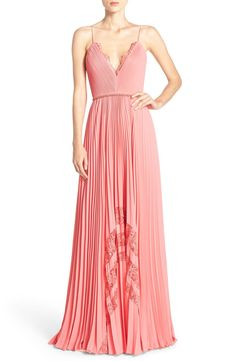 Tiny meticulous pleats ease the flowing, ethereal silhouette of this classically femme evening gown from Badgley Mischka. It's also suspended by delicate spaghetti straps and trimmed with floral lace insets.