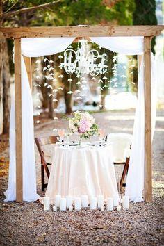 une arche mariage en bois décorée de lustre, rideaux blancs et une suspensions romantique