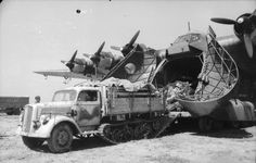 A German  Me 323 Gigant transport aircraft unloading a half-track. Italy , unknown location, 1943.