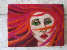 textile art. This wet felted picture shows a girl with the wind blowing through her hair making it flow across her face. The hair is in vibrant pinks, oranges and reds. She has intense, green eyes and full, red lips. I have never made a felted human face before and had to needle felt many fine layers of wool over each other in order to make the shadows with give the image depth. When the felt was dry I added free machine sttching to add more movement in her hair. I had a lot of fun with the…