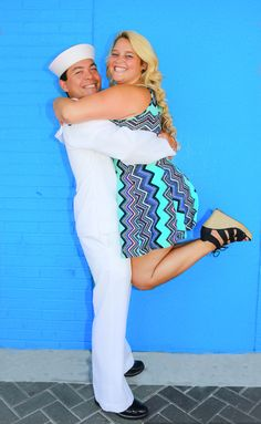 Navy husband & wife had family pictures done prior to his deployment at Jacksonville Florida beach ... She wore bright colors to compliment his uniform ... There son was incorporated into some pictures with his beautiful blue eyes ... & we used a famous blue wall! And can't forget they got to dance in the streets