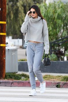 Kendall Jenner wears a cozy turtleneck sweater, gray sweatpants, Adidas sneakers, aviator sunglasses, and a mini Givenchy duffle bag