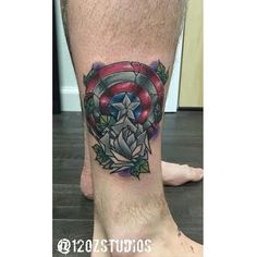 Awesome full color Captain America shield comic book superhero with grey rose male ankle calf tattoo by Chris Curtis.