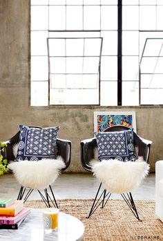 Two black armchairs, blue patterned pillows and sheepskin rugs