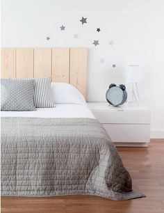 Wood headboard, it could be done with pallets, white nightstand table. Nordic style.