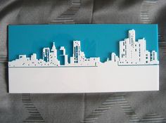 Laser cut detroit skyline - The image was laser cut from white & blue acrylic plastic. I glued the two peices together with super glue. The two peices of plastic give a cool 3D effect.