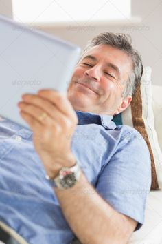 Happy mature man using a tablet pc lying on a sofa in a living room ...  50s, Abode, Short Hair, apartment, brown eyes, calm, casual, caucasian, cheerful, content, couch, digital tablet, domicile, grey hair, happy, home, homey, house, indoors, leisure, lifestyle, living room, lying, male, man, mature adult, peaceful, relaxed, relaxing, scrolling, shirt, sitting room, smiling, sofa, tablet, tablet computer, tablet pc, touching, touchscreen, using