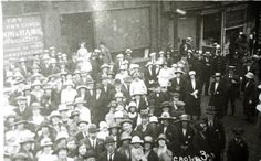 Scarce Halliwell real photo postcard showing crowds watching a procession at Radcliffe, near Bury. A shop in the background is advertising bacon and ham.