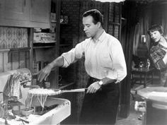 """Jack Lemmon draining spaghetti with a tennis racket while Shirley Maclaine looks on in """"The Apartment."""""""
