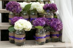 Gorgeous mason jar flowers - I think I'd do purple and white ribbons on the opposite flower color!
