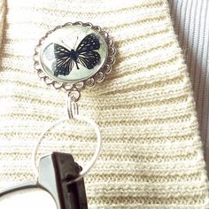 This eyeglass holder is magnetic and is decorated with a black butterfly on a background of a vintage postcard.  The image is protected and magnified by a glass