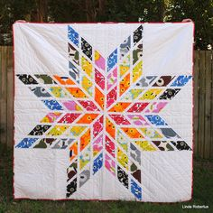 """This Modern Lone Star Quilt by Linda Robertus of Blue Jacaranda is a stunning burst of color. Linda used the iconic Unikko (Poppy) print from MARIMEKKO in nine different colorways for the front along with a gorgeous whole cloth print called Hetkiä for the back. """"I quilted this Modern Lone Star (affectionately known as Starimekko) in straight lines through the diamonds, ½"""" from the seams, continuing in the white spaces outside the star, using a walking foot and white Aurifil 40wt thread."""" ..."""