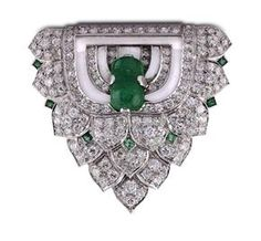 RENE BOIVIN. AN EMERALD AND DIAMOND CLIP BROOCH.  The shield-shaped plaque composed of foliate sections set with brilliant-cut diamonds, interspersed with square-cut emeralds, to a central sugar-loaf emerald within an odeonesque concentric pattern of polished gold. French assay mark and maker's mark. Accompanied by a certificate from Francoise Cailles stating the date of manufacture to be 1935.