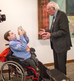Democratic presidential hopeful Bernie Sanders does an interview with Justin Chappell, a reporter in a wheelchair, in Des Moines, Iowa.