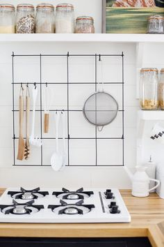 cheap kitchen organization: hang a wire rack above the stove to store cooking…