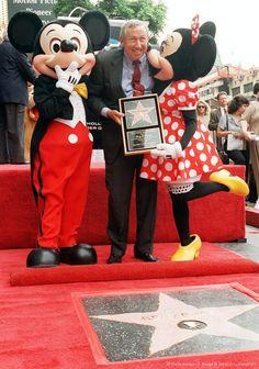 Minnie Mouse gives a kiss to Roy E. Disney.