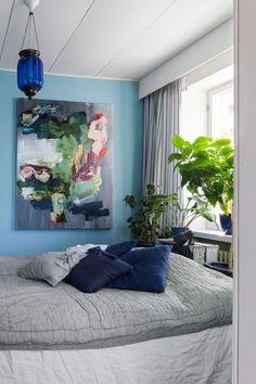 Sinisävyisen makuuhuoneen seinällä on Royn maalaus Aloita ryhmänäköpuheluiden soittaminen tänään.
