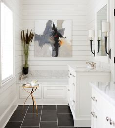Huff Harrington Cottage Renovation: The master bath.   Black honed slate and Alabaster-painted cabinetry with marble countertops. A Charles Ross painting hangs over the tub.
