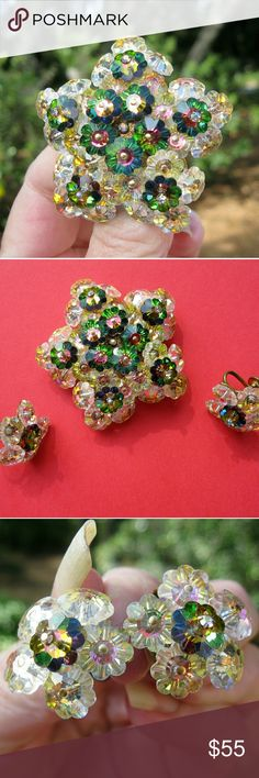 "Vintage AB & Green Margarita Crystal Brooch Set Late 1950s crystal Margarita rhinestone brooch and earrings featuring colors of aurora borealis and green.  These three dimensional beauties feature petals of ""Pools of Light"" aurora  borealis crystals topped with heliotrope green crystals and a stamen of tiny AB rhinestone crystals.  There is a wire on the brooch back which could also convert it to a pendant.  Gold tone metal backing is darker on the screw back earrings than on the brooch.  No…"