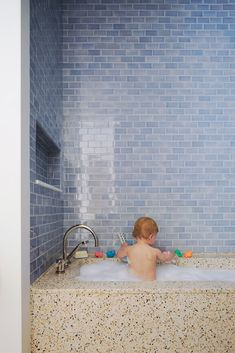 Not sure if I love this because of the cute baby or the color of the tiles!   Watery blue subway tile and terrazzo bath or pebblecrete