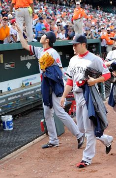 BALTIMORE, MD - JULY 28: Koji Uehara #19 of the Boston Red Sox tosses a ball to a fan after a 5-0 victory against the Baltimore Orioles at Oriole Park at Camden Yards on July 28, 2013 in Baltimore, Maryland. (Photo by Greg Fiume/Getty Images)