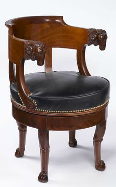 Mary Helen McCoy Fine Antiques | An important and rare French Empire period, mahogany fauteuil de bureau à assise tournante with a gondola shaped back and a leather swivel seat attributed to François-Honoré-Georges Jacob-Desmalter. There is an exceptional carved ram's head at each arm. The fauteuil rests on four legs ending with lion paw feet.