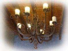 """This hand made iron chandelier is produced in various sizes and rustic color options. The chandelier """"Los Ángeles"""" comes with rusted finishing, natural or as black iron. It is often used for illuminating high ceiling living rooms, foyer and house entries. Foyer Chandelier, Chandelier Ceiling Lights, Ceiling Lamp, Wall Lights, Candle Sconces, Wall Sconces, Hotel Foyer, High Ceiling Living Room, Iron Chandeliers"""