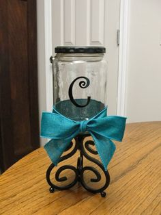 candy jar made from a pickle jar, glued to candle holder, painted lid, added bow and letter