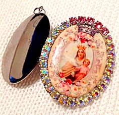 Vintage porcelain cameo locket pendant featuring the Blessed Mother Virgin Mary wearing a crown and holding the baby Jesus. They are surrounded by pink roses. Pink and aurora borealis rhinestones. The silver tone locket can hold 2 photo's or prayer petition requests to the Holy Mother.  Large size of 2 inches long and 1.5 inches wide. See photo with quarter for inside size comparison
