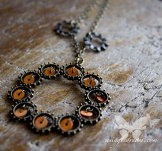 Simulating Flowers  Upcycled from a broken necklace, this large bronze pendant, adorned with tiny discs of cheerful nectarine is flanked by a pair of blackened bronze cogs masquerading as tiny flowers.  Sure, this piece could be classified as Steampunk if it suits your fancy, but it would...