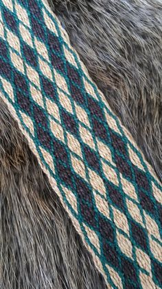 Hand made using tablet weaving or card weaving technique. This strap is 2 inches wide and adjustable from 32 inches to 56 inches. It is woven