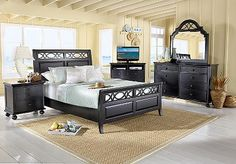 Come home to the vacation resort style of the Seaside bedroom. It features a graceful sleigh bed, lattice design and raised panel details. The black finish is rubbed through and distressed for an antiqued look. For a splash of color, add a colorful chest or media base. (Coordinating pieces sold separately.)