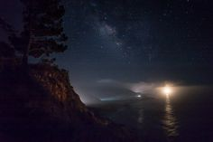 Night at Big Sur California. Fog on the Pacific with car lights illuminating the fog. The bright light is the Big Sur lighthouse. [2000x1336][OC]
