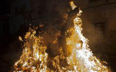 Homem passa com seu cavalo através das chamas de uma fogueira na vila de San Bartolomé de los Piñares, na Espanha. As fogueiras são armadas ...