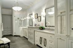 This traditional bathroom features a clean and classic look created by white wood cabinets and crisp gray floor tiles. Mirrored panels in some of the cabinet doors help visually widen the space.